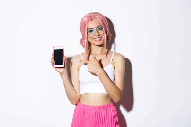 Portrait of happy beautiful female model in pink glamour wig and bright makeup, pointing finger at mobile phone screen, showing application or banner.