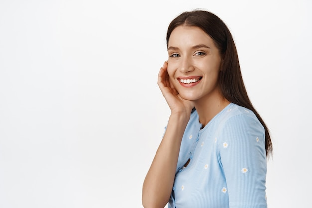 Portrait of happy beautiful female model, smiling white teeth, touching cheek, advertisement of skincare products, cosmetics or makeup, standing on white.
