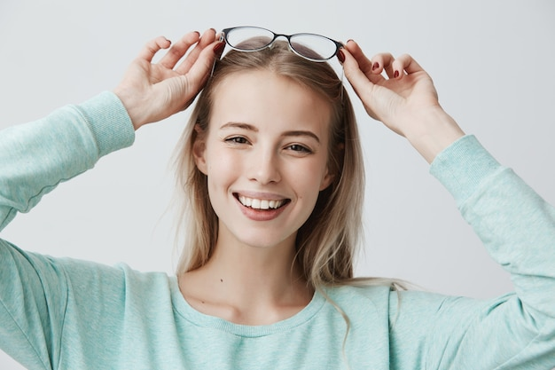 Portrait of happy beautiful female with blonde long hair and spectacles