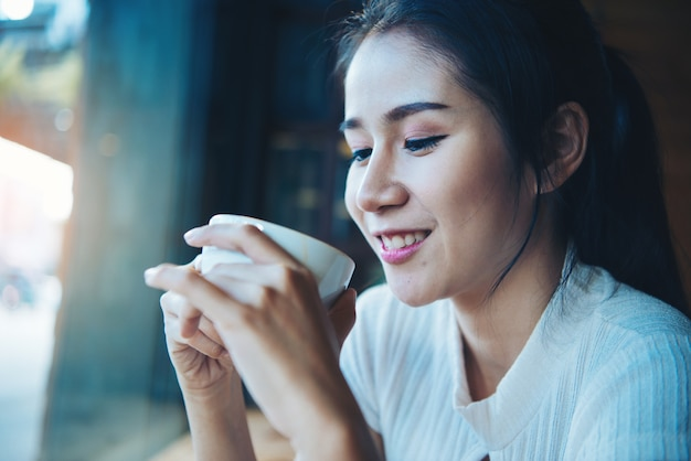 Portrait of happy beautiful female with mug in hands