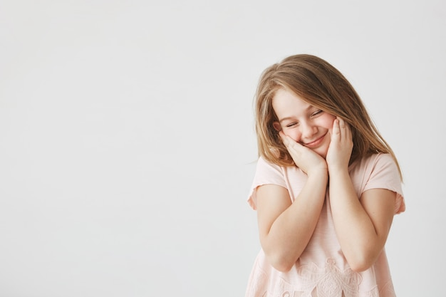 Portrait of happy beautiful girl with blond hair in pink t-shirt squeezing face with hands, closing eyes, feeling shy after cute boy in school made her compliment