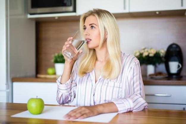Portrait of happy beautiful woman drinking water in modern kitchen
