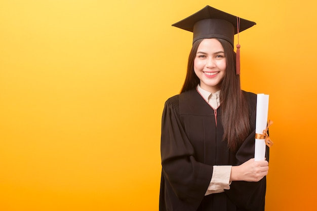 Portrait of happy beautiful woman in graduation gown is holding education certificate on yellow background