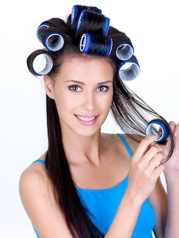 Ritratto di bella donna felice in hairrollers - isolato su priorità bassa bianca
