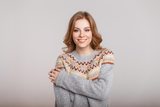 Portrait of a happy beautiful woman in a sweater on a gray background