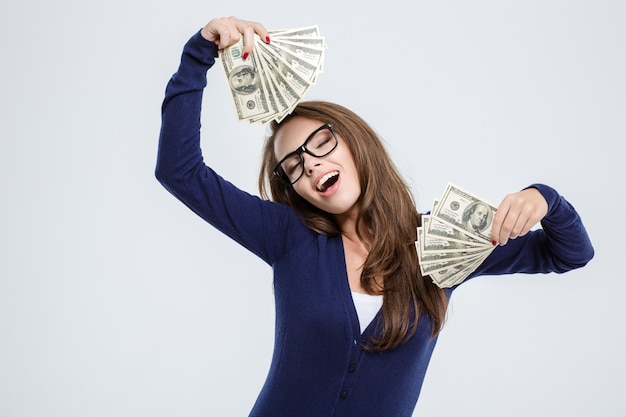 Portrait of a happy beautiful woman with closed eyes holding money isolated on a white background