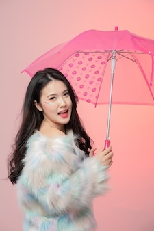 Portrait of happy beautiful young asian woman holding umbrella