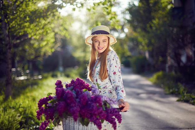 Portrait of a happy beautiful young girl with vintage bicycle and flowers on city background in the sunlight outdoor. bike with basket full of flowers. active leisure concept.