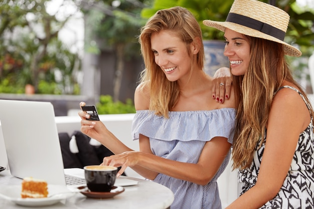 Portrait of happy best female friends pay with credit card, use banking application on modern laptop computer, make orders, drink aromatic coffee with piece of cake. online purchase concept.