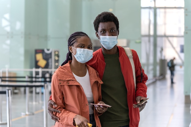 Portrait of happy black couple in face masks hold boarding passes and passports in the airport