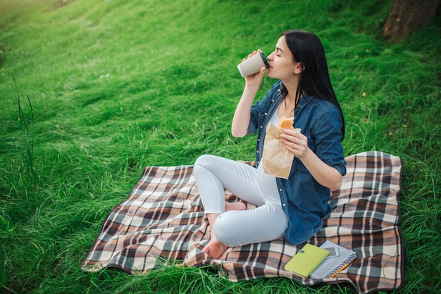 Portrait of a happy black hair and proud pregnant woman in a city in the park . photo of female model touching her belly with hands. the female model is sitting on grass and drinking coffee or tea.