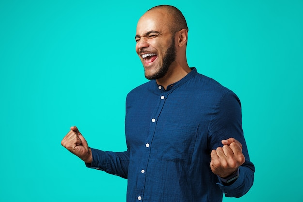 Portrait of a happy black man celebrating his success expressing joy on turquoise