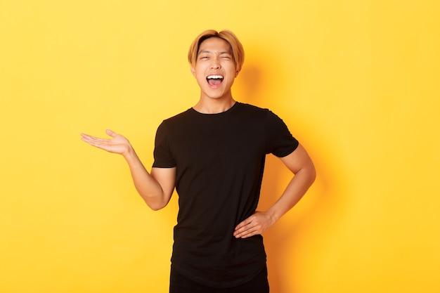 Ritratto di felice ragazzo asiatico biondo, ammiccante impertinente e sorridente, tenendo in mano qualcosa sopra il muro giallo