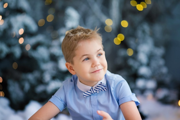 Portrait of happy blonde child boy in blue shirt front of the snowy winter decorated tree
