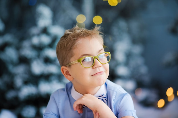 Portrait of happy blonde child boy in blue shirt with big glasses