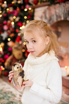 Portrait of happy blonde child girl in white sweater holding toy owl
