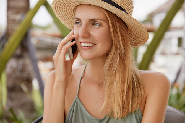 Portrait of happy blonde female wears straw hat and happy smile, looks positively away, has pleasant talk with boyfriend via cell phone, shares impressions about being on beach resort. people and talk