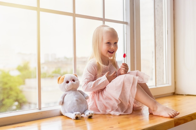 Portrait of happy blonde girl wearing pink dress holding a lollipop while sitting with a toy on a window sill