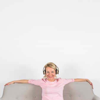Portrait of a happy blonde mature woman sitting on sofa listening music on headphone against white background