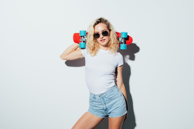 Portrait of a happy blonde woman in sunglasses posing with skateboard while standing and laughing isolated over white wall