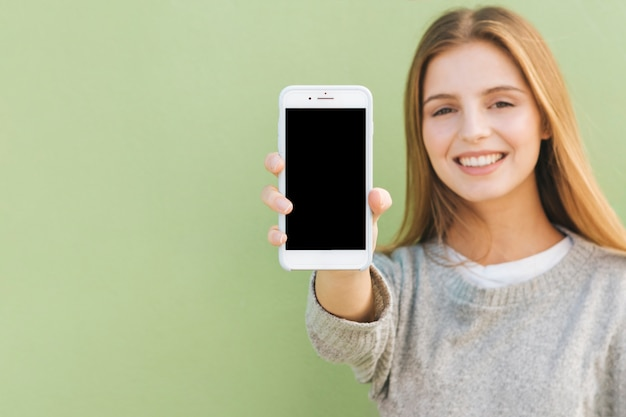 Portrait of a happy blonde young woman showing mobile phone against green backdrop