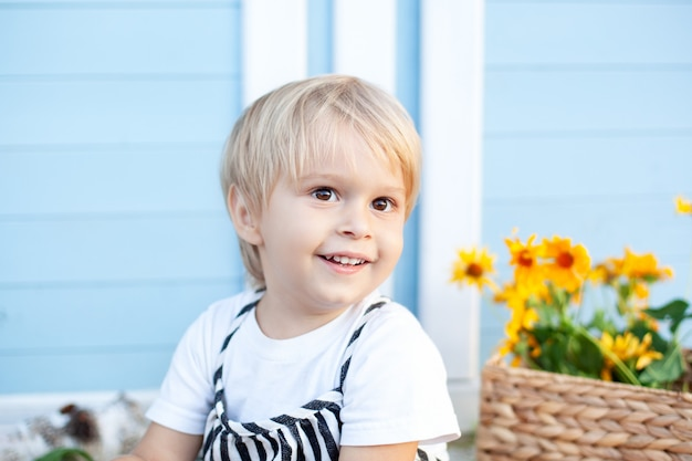 Portrait of a happy blondy haired boy child smiles enjoys life. portrait of a young boy in nature, park, outdoors. the concept of a happy family and parenting. childhood concept. charming baby. summer