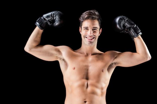Portrait of happy boxer showing muscles