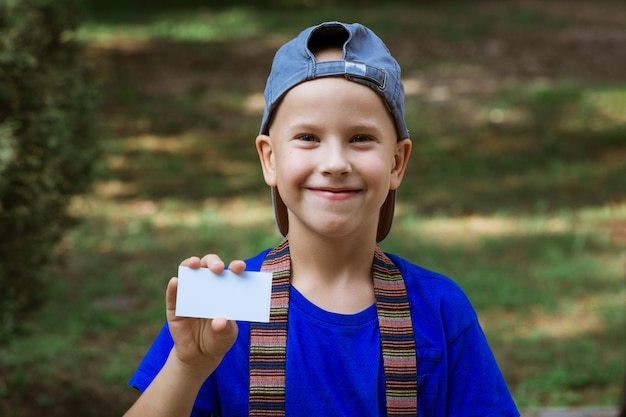 Portrait of a happy boy in a cap in a blue tshirt holding a business card in the park