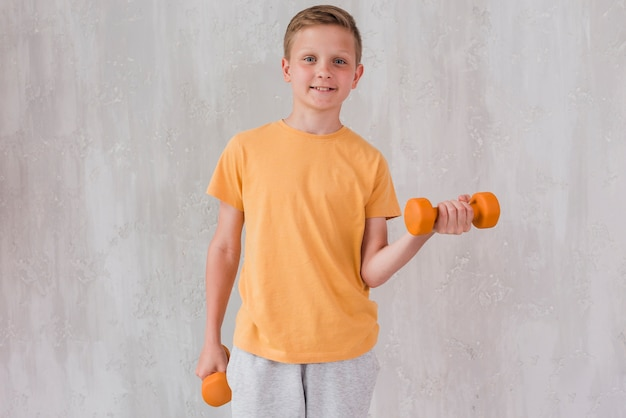 Portrait of a happy boy exercising with dumbbell standing in front of concrete wall