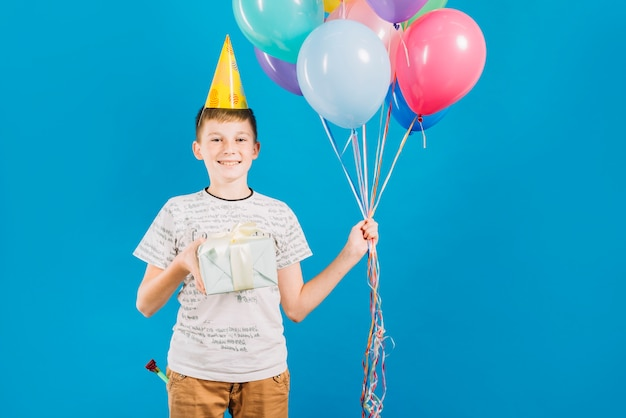 Portrait of a happy boy holding colorful balloons and birthday gift on blue background