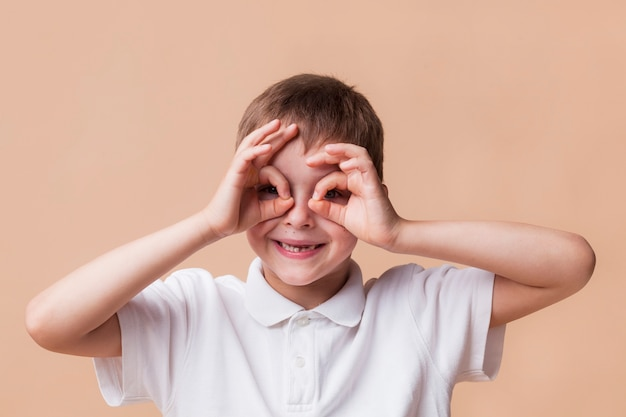 Portrait of happy boy looking through fingers as binoculars