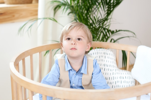 Portrait of a happy boy playing in a baby cot. the boy sits alone in a crib in the nursery. the lonely child stays in the crib. a child in bed is smiling, a boy is in a white bed in kindergarten.