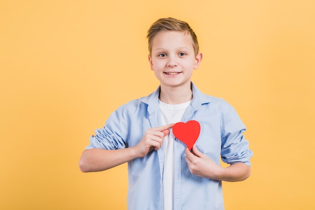 Portrait of a happy boy showing red heart near his chest against yellow background