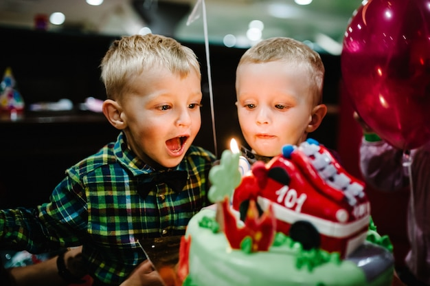 Portrait of happy boys, kids, baby for three years celebrating birthday party blowing at candles on cake
