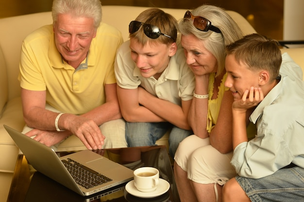Portrait of a happy boys with grandparents and laptop