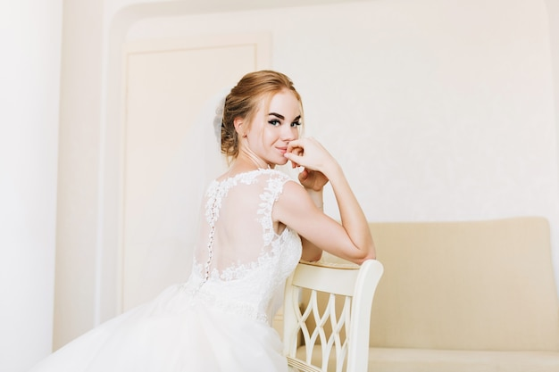 Portrait happy bride in wedding dress in appartment sitting on chair.