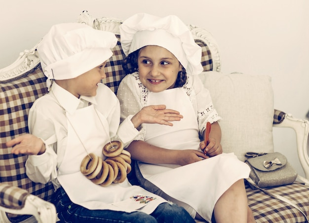 Portrait of happy brother and sister as a chef discussing recipe
