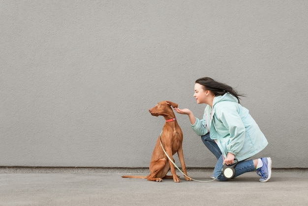 Portrait of a happy brunette woman in casual clothes in the street with a dog on a leash