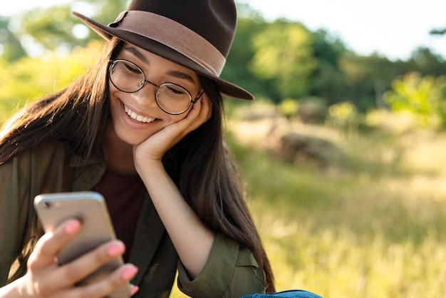 Portrait of happy brunette woman wearing stylish hat and eyeglasses using cellphone while walking in green park on sunny day