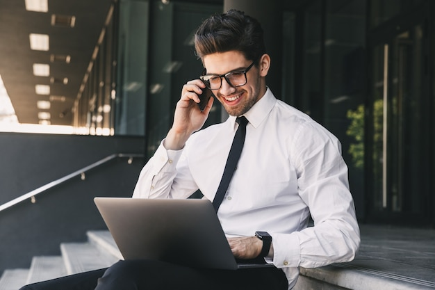 Portrait of happy businessman dressed in formal suit sitting outside glass building with laptop, and speaking on cell phone