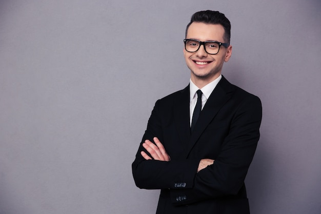 Portrait of a happy businessman in glasses standing with arms folded over gray wall and