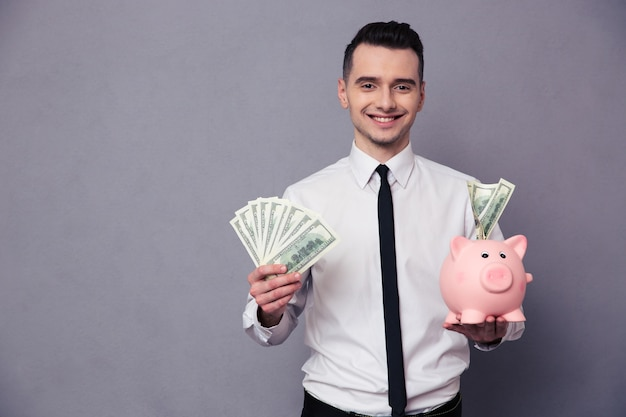 Portrait of a happy businessman holding pig money box and money over gray wall