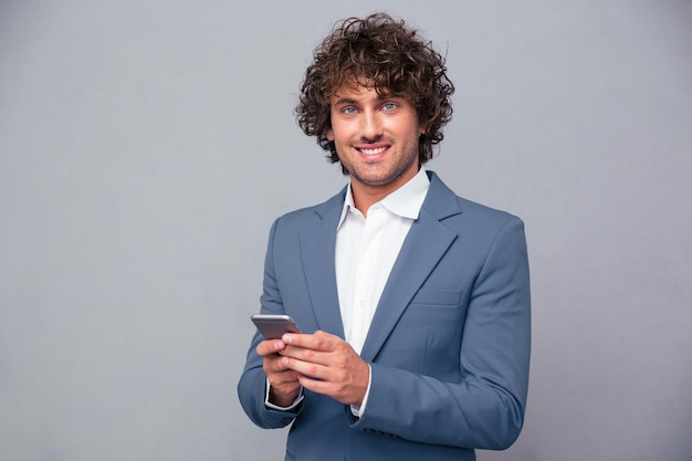 Portrait of a happy businessman holding smartphone and looking at camera over gray wall
