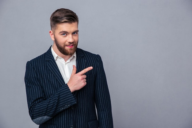 Portrait of a happy businessman pointing finger away over gray wall