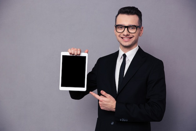 Portrait of a happy businessman showing blank tablet computer screen over gray wall