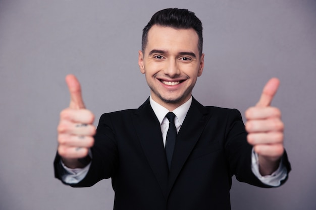 Portrait of a happy businessman showing thumbs up over gray wall