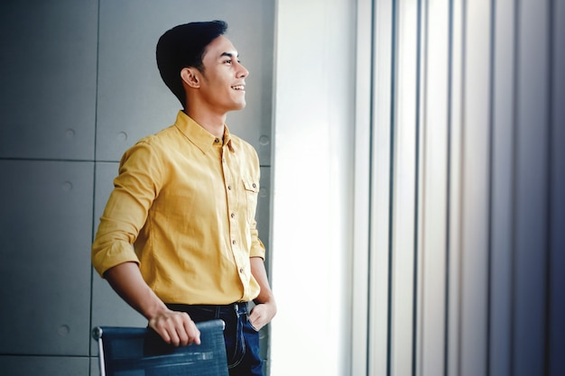 Portrait of happy businessman standing by the window in office. looking away and smiling. dreaming for success