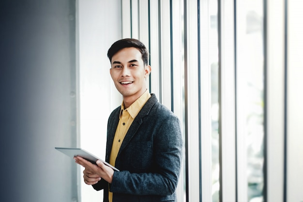 Portrait of happy businessman standing by the window in office