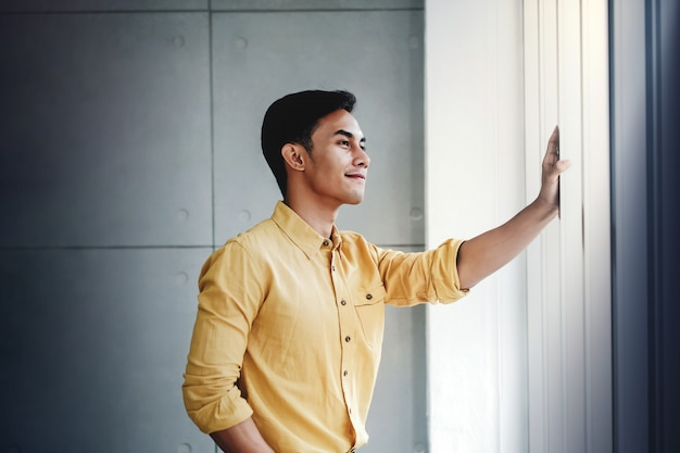 Portrait of happy businessman standing by the window in office.