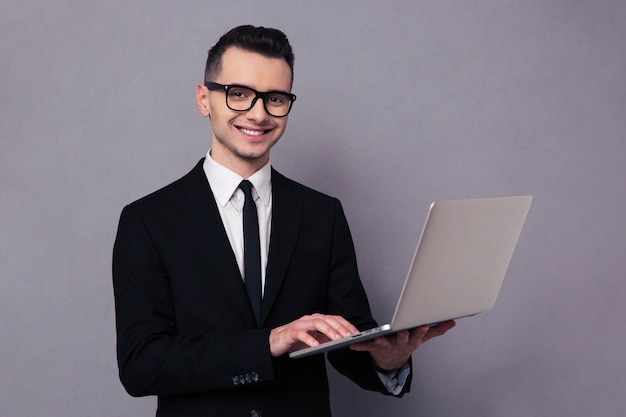 Portrait of a happy businessman using laptop computer over gray wall